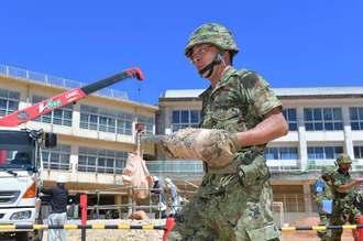 処理した米国製5インチ艦砲弾を運ぶ陸上自衛隊の隊員=2日午前10時48分、那覇市久米・天妃小学校運動場