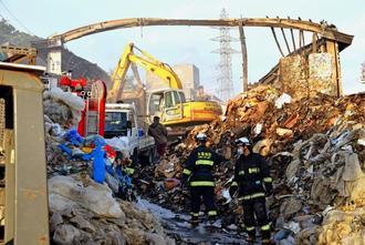 重機で工場の鉄骨を解体した後、消防隊員が施設内の消火に当たった=3日午後4時55分ごろ、糸満市大里
