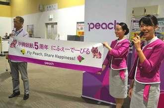 乗客に沖縄就航5周年の感謝を伝えるピーチのスタッフら=18日、那覇空港LCCターミナル