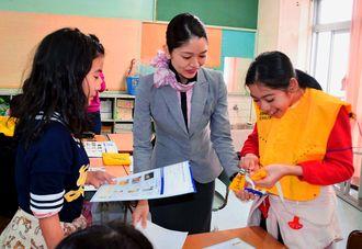 キャビンアテンダント(中央)からライフベストの着用や説明を教わる児童たち=23日、那覇市・上間小学校