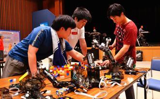 ロボットアームを修正する出展者=9日、那覇市久茂地・タイムスビル