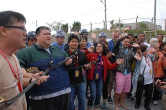 辺野古新基地建設の抗議行動を続ける市民らと交流する「御冠船歌舞団」のメンバーら=18日午前、名護市・キャンプ・シュワブのゲート前