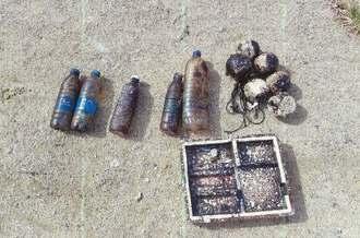 国頭村の北側の海岸で見つかった油状のものが付着したペットボトルや漁具など=9日、同村(中城海上保安部提供)