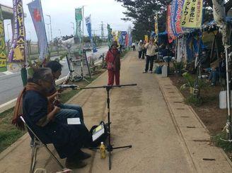 米軍キャンプ・シュワブゲート前で、新基地建設に反対し歌を歌う女性たち=25日、名護市辺野古