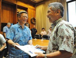 会談でイゲ知事(右)へかりゆしウエアを贈る翁長雄志知事=9日、ホノルル市・ハワイ州庁