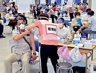 高齢者向けの新型コロナウイルスワクチン接種を受ける対象者ら=15日午後6時52分、宜野湾市・沖縄コンベンションセンター(画像を加工しています)