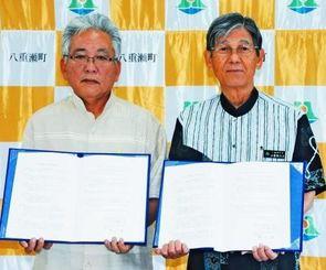 災害時の支援協力で調印を交わした濱元清会長(左)と比屋根方次町長=5日、八重瀬町役場
