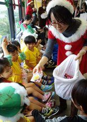 サンタ姿のモノレール社員(右)からお菓子などのプレゼントをもらい笑顔の保育園児たち=24日午前、那覇市内
