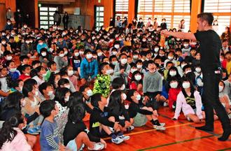 MASAさん(右)のマジックに声を上げて驚く子どもたち=18日、宜野湾市・長田小学校