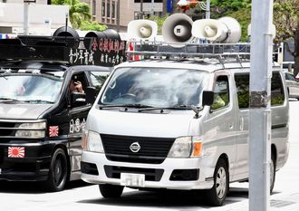 「阿部記者は犯罪者」などとスピーカーを響かせる正体不明の街宣車(右)=6月、那覇市役所前
