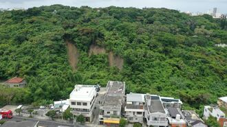 幅80メートルにわたり崩れた山の斜面=18日午前11時半すぎ、那覇市繁多川の金城ダム近く(小型無人機で撮影)