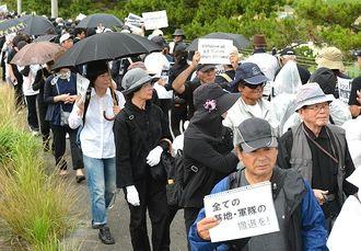 うるま市の女性遺体遺棄事件を受け、無言で抗議の意思を示し行進する集会参加者=22日、北中城村石平・キャンプ瑞慶覧前