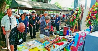 沖縄の菓子などが供えられた「沖縄の塔」前で手を合わせる遺族ら=28日、フィリピン・ダバオ市(沖縄ツーリスト提供)
