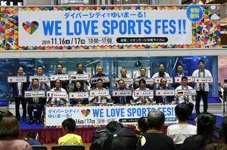 世界各国の言葉で「ようこそ」と書かれたボードを手にするラグビー日本代表の田村優選手(前列左から4人目)、ハンドボール日本代表の宮﨑大輔選手(同6人目)ら=17日、北中城村・イオンモール沖縄ライカム