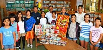 タコライス文庫の図書を囲む金武町商工会や金武小学校の児童ら=金武町・同小