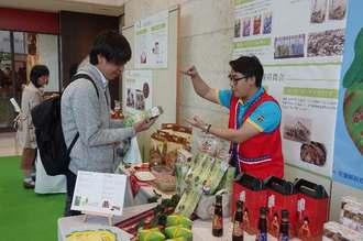 花蓮の特産品を品定めする来場者(左)ら=14日午前、那覇市久茂地のタイムスビル