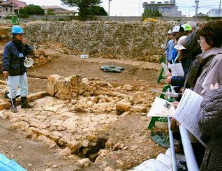 井戸周辺の水場の遺跡について説明する県立埋蔵文化財センターの発掘担当者(左)=21日、那覇市の首里高校グラウンド