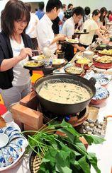 ぐしちゃんいい菜(手前)を使った料理を皿に盛る、試食会参加者=八重瀬町玻名城のザ・サザンリンクスリゾートホテル