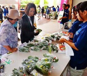 高校生が育てた新鮮野菜を買い求める来場者=石垣市大川、同校