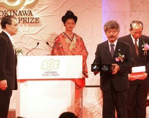 稲嶺知事(左)から沖縄平和賞の記念品を受け取る中村哲氏(右から2人目)=2002年8月30日、名護市の万国津梁館