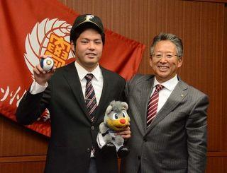 日本ハムとの仮契約を済ませ、笑顔をみせる高良一輝(左)と原田豊スカウト=福岡県・九州産業大