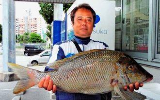 座間味で61.6センチ、4.5キロのタマンを釣った新城光夫さん=20日