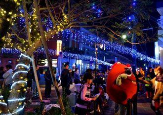 青や黄色のイルミネーションに彩られた商店街。町のキャラクターいもっちも参加し、点灯式を盛り上げた=11月29日、嘉手納町新町通り