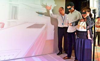 3Dめがねを装着し、仮想空間住宅を体験する来場者=14日、宜野湾市・沖縄コンベンションセンター