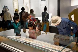 リニューアルされた高知県立坂本龍馬記念館で、展示資料を見る来館者=21日午前、高知市