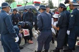 名護市辺野古の新基地建設に反対しゲート前に座り込む市民らを強制排除する機動隊員=11日午前、名護市辺野古の米軍キャンプ・シュワブゲート前