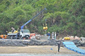 沖縄防衛局と書かれた浮き標識を砂浜に降ろす作業員=13日午後2時10分、名護市辺野古のキャンプ・シュワブ=