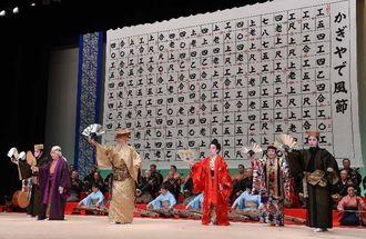 正午の時報を合図に始まった三線の合奏に合わせ、「かぎやで風節」を踊る出演者=4日、読谷村文化センター鳳ホール