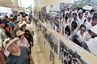 AIでカラー化された報道写真に見入る来場者=25日、那覇市久茂地・タイムスビル1階エントランス