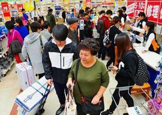 免税専用レジで家電製品を購入する観光客ら=9日午後、那覇市おもろまち、エディオン那覇メインプレイス店