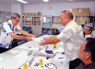 沖縄・自民の島袋大代表(右)へ回答書を手渡す金城弘昌総務部長(左)=9日、県議会