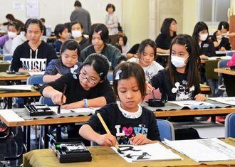 真剣な表情で筆を動かす子どもたち=18日、沖縄市中央公民館