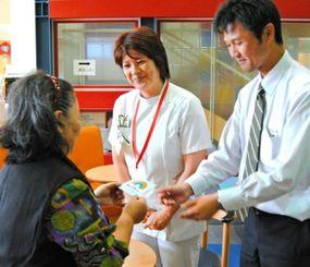 退院時に「なんこいカード」を受け取る70代の女性(左)。「安心して転院できる」と話していた=南風原町、県立南部医療センター・こども医療センター