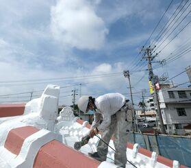 「梅雨明けしたらこれから注文が増えるかも」と屋根の補修作業に汗を流す作業員=2日午前11時02分ごろ、与那原町(古謝克公撮影)