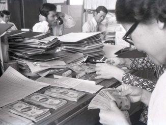 最後のドル建て給料 政府公務員の給料日。ドル建て最後の支給とあって、職員は感慨深げだった=1972年5月2日