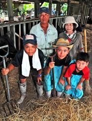 牛馬の世話を手伝う(前列左から)大里中1年の知念舜さんと新垣優太さん、大里北小5年の國吉夏輝君、(後列左から)畜産農家の國吉光男・千代さん夫妻=22日、南城市大里古堅