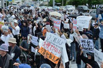 在沖米軍司令部があるキャンプ瑞慶覧に向かってプラカードを掲げ、米軍属による女性遺体遺棄事件に無言で抗議する参加者たち=22日午後2時50分、北中城村の石平ゲート前
