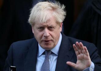 英首相官邸から下院へ向かうジョンソン首相=19日、ロンドン(ロイター=共同)