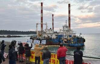 離岸作業をする座礁船と辺野古新基地建設に抗議する市民ら=14日午前7時34分、恩納村名嘉真