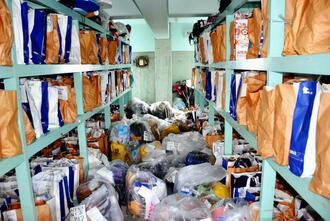 保管庫に設置されている棚に収まりきれず足場にも置かれている取得物=5月20日、豊見城署