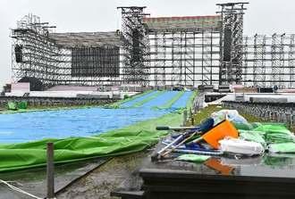 AKB48の屋外コンサート中止が決まり、雨が降る中、解体作業が進む会場=16日午後、豊見城市の豊崎海浜公園