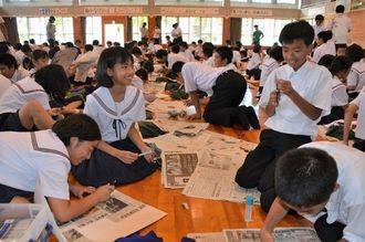 選んだ記事を持ち寄って切り抜き新聞をつくる1年生=6月28日、寄宮中学校