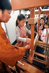 久米島紬の織りを体験する子どもたち=那覇市久茂地・タイムスビル