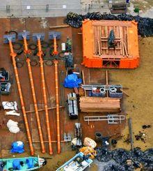 米軍キャンプ・シュワブの海岸に置かれた、海底ボーリング調査で使用するとみられる台船(右上)と支柱=16日午前11時36分、名護市辺野古で共同通信社ヘリから