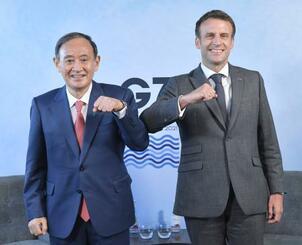 会談を前に肘タッチを交わす菅首相(左)とフランスのマクロン大統領=12日、英コーンウォール(共同)