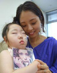 長女りん香ちゃん(左)を抱く佐々木そよ香さん。「胎教音楽もずっと、安室ちゃんの曲でした」と話す=沖縄タイムス社